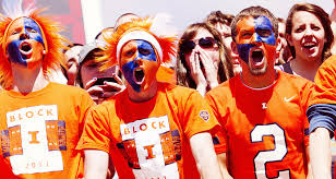 Students with orange and blue painted faces at Illinois football game